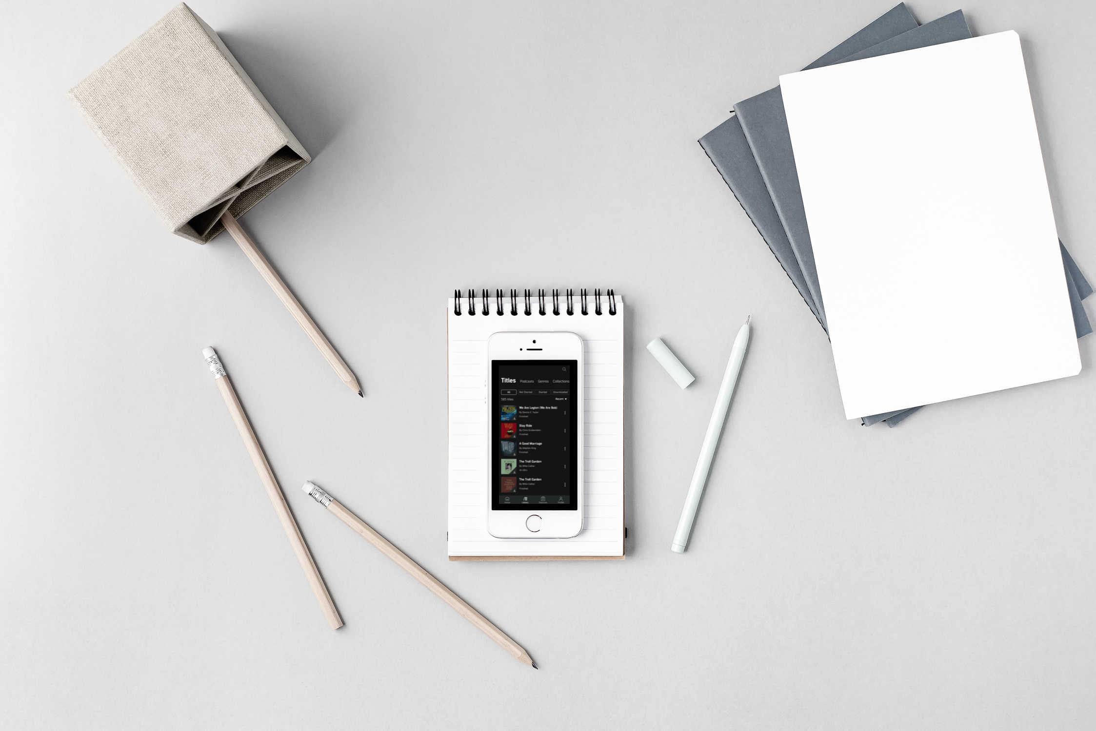 flat lay of smart phone, pencils, and notebooks