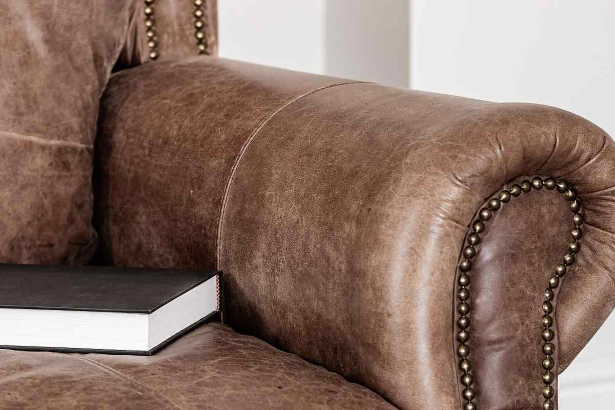 old brown leather chair with hardback book resting on top