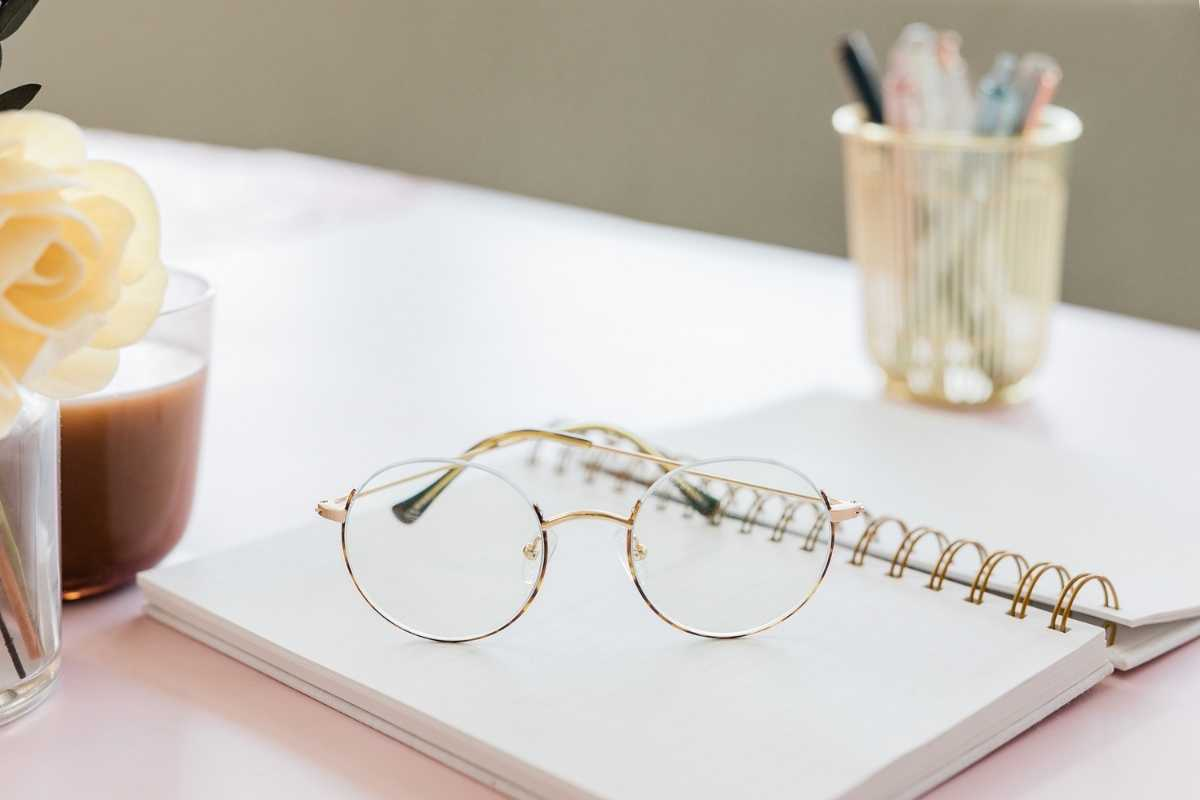 open notebook on desk with gold glasses on top