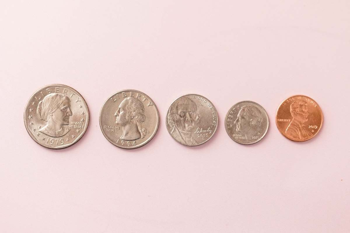 five coins on pink background
