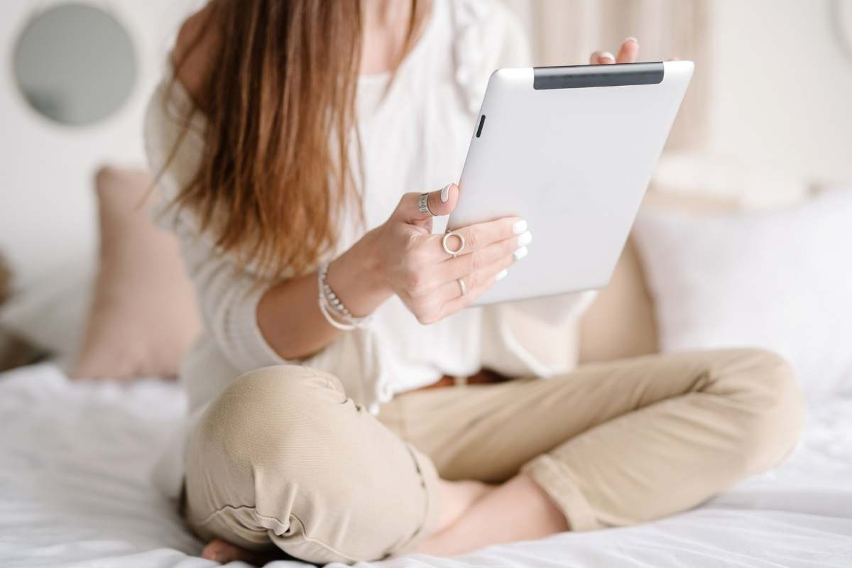 woman on bed with clipboard