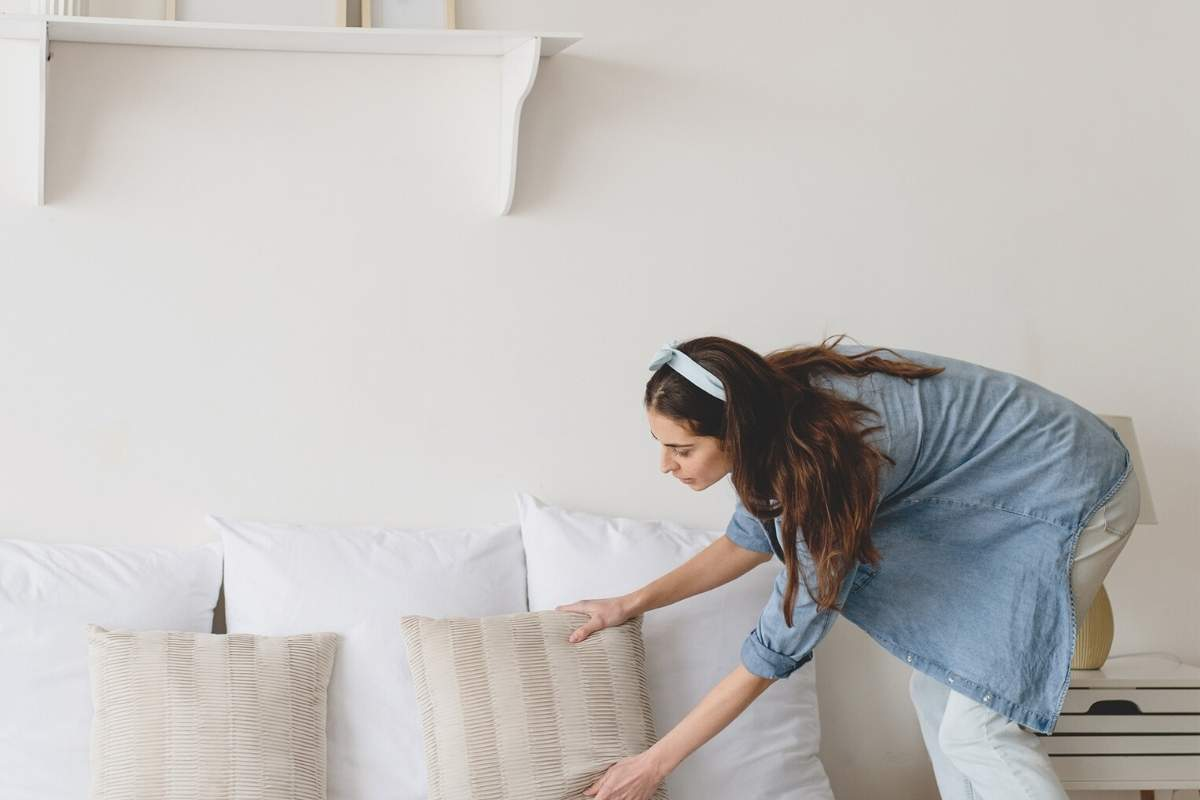 woman arranging pillows on bed
