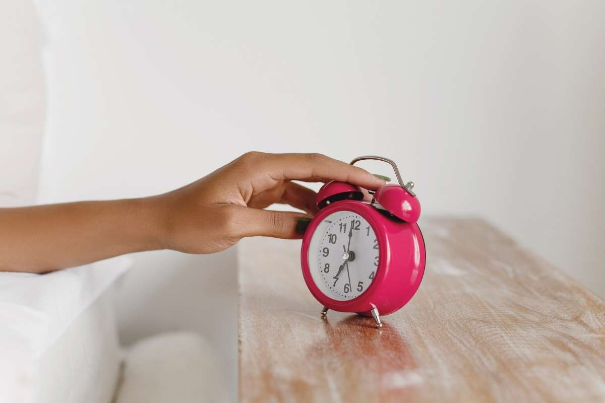 hand pushing snooze button on pink alarm clock