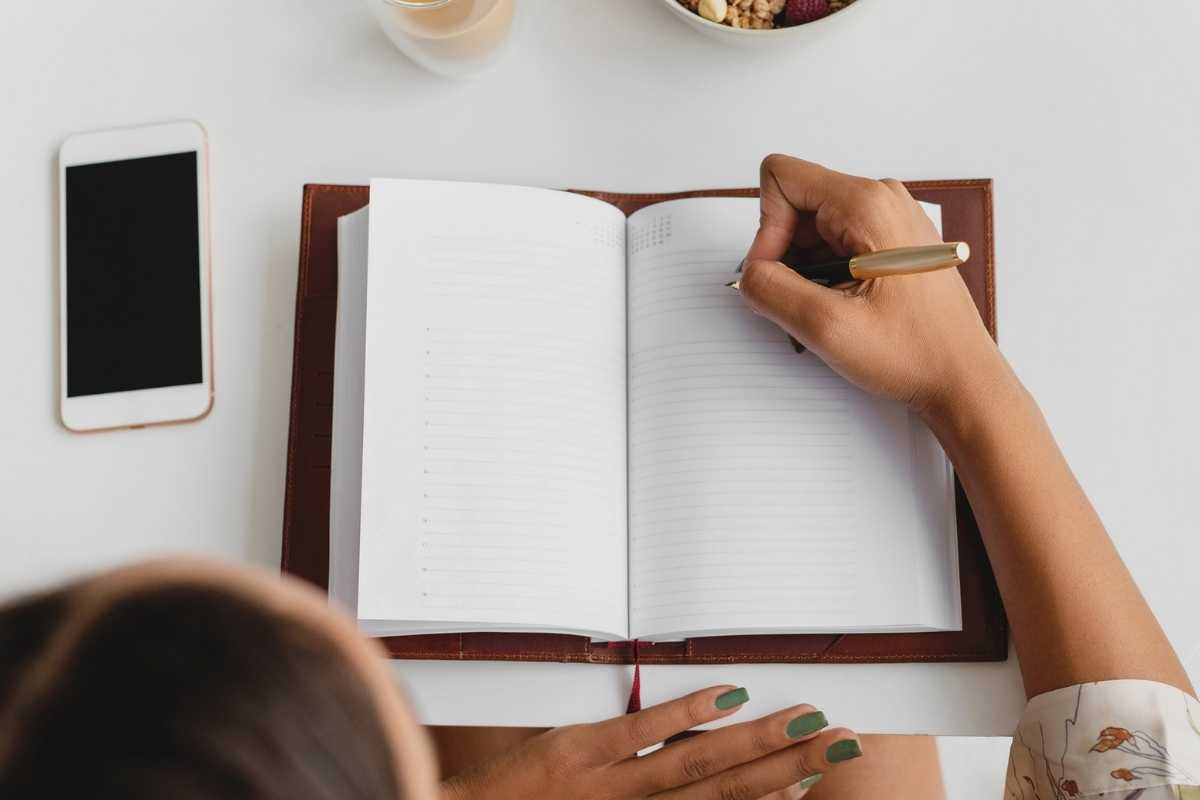 woman writing in journal on table