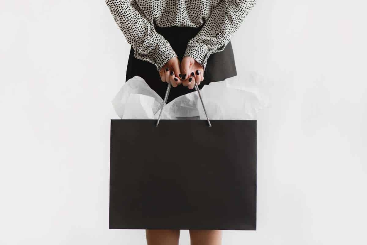 woman holding shopping bags behind her back