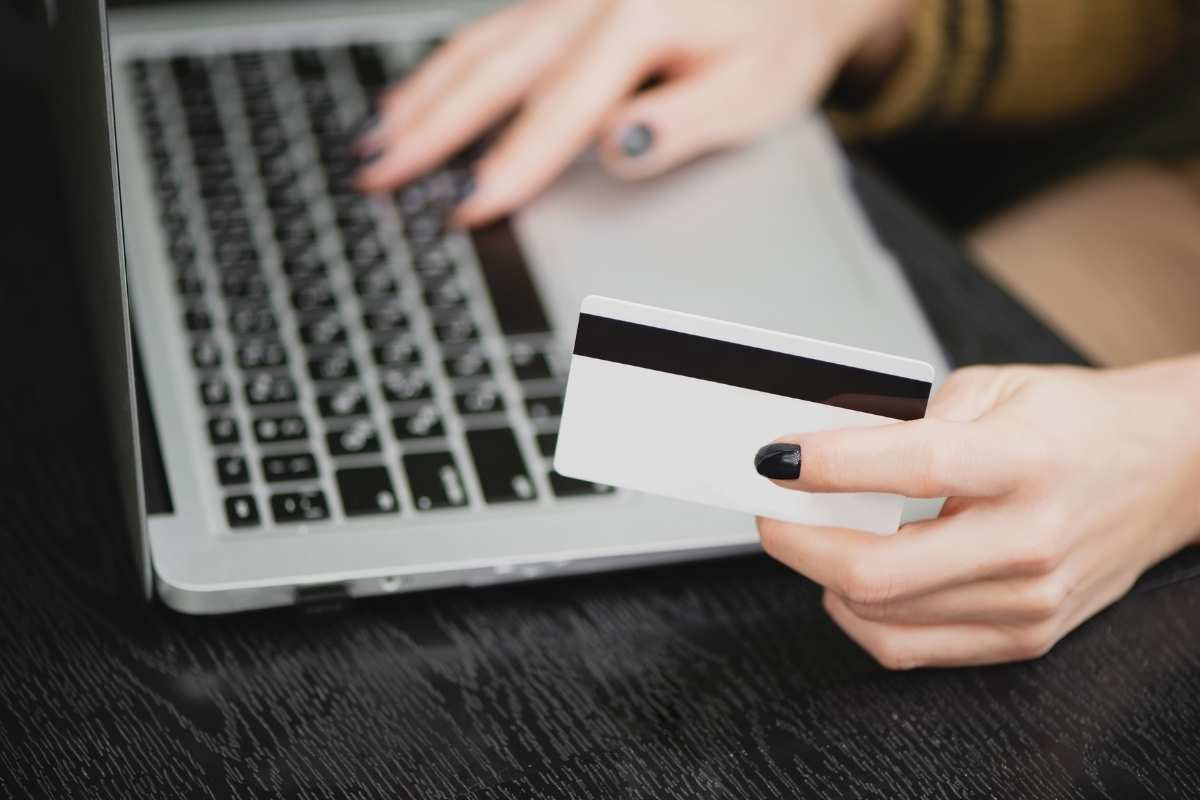 credit card and laptop on woman's desk