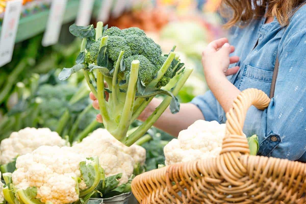 woman holding fresh broccoli at store
