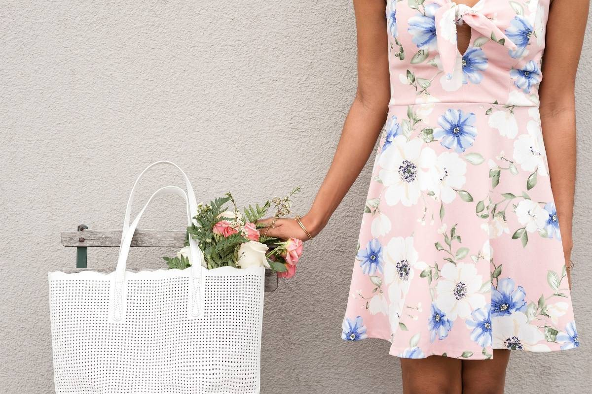 woman in pink dress next to bag of flowers