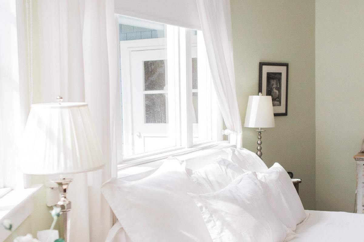 green bedroom with white curtains