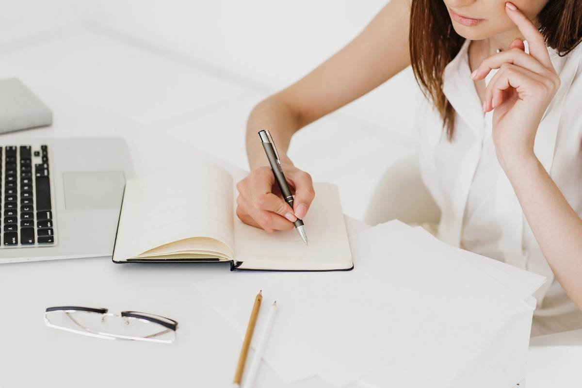woman with planner at white table