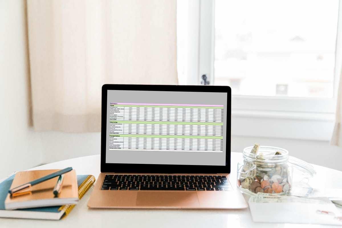 laptop on desk showing budgeting spreadsheet