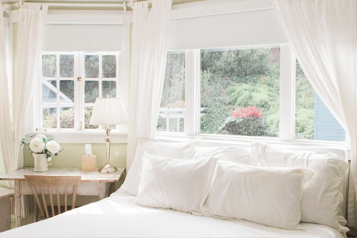 a very clean bedroom with big windows