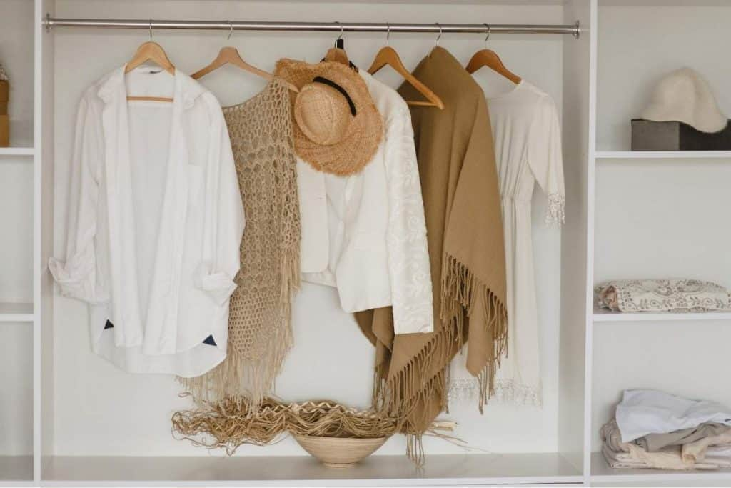 minimal closet with brown sweaters and hat