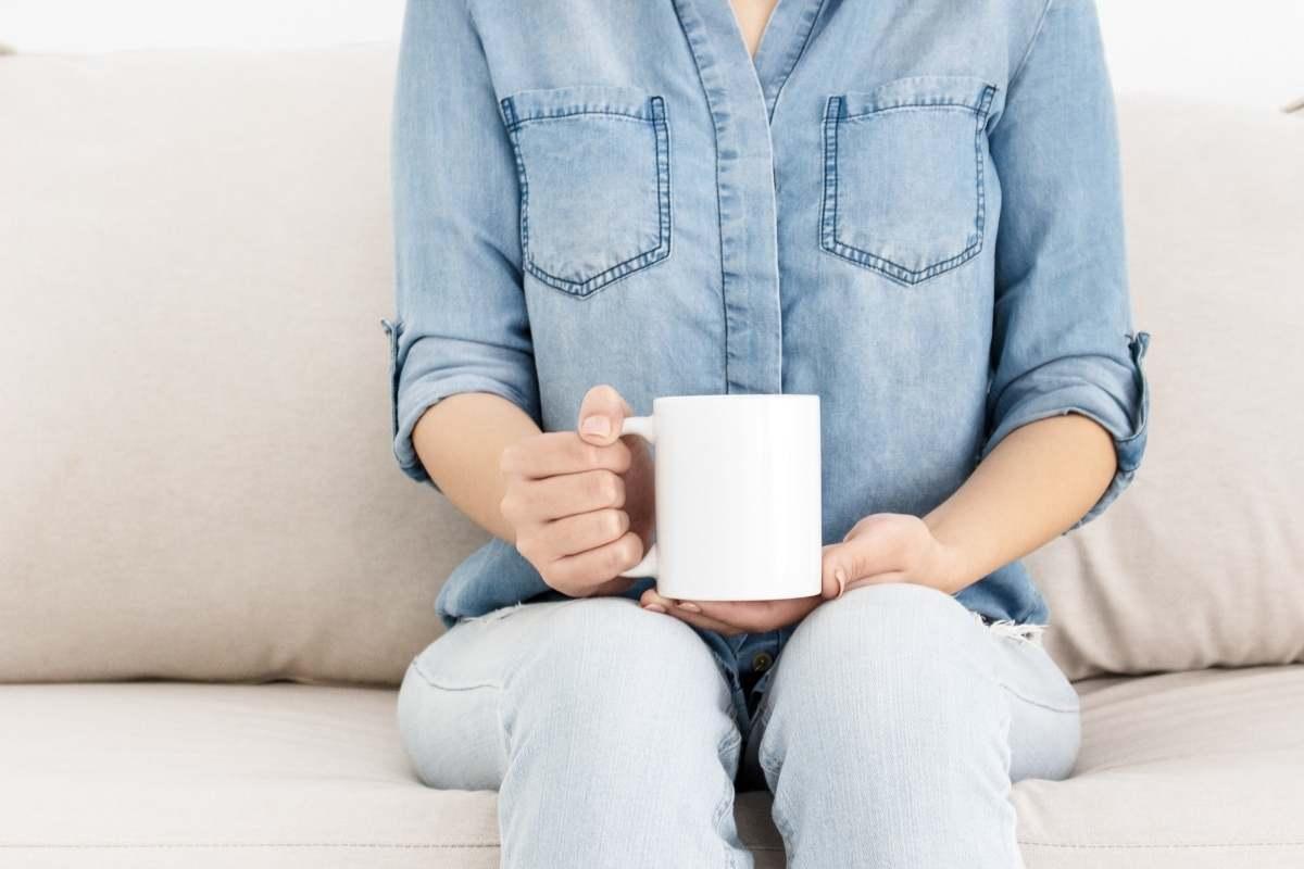 woman in blue shirt holding coffee mug